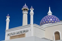 White Islamic Mosque with blue dome against blue sky