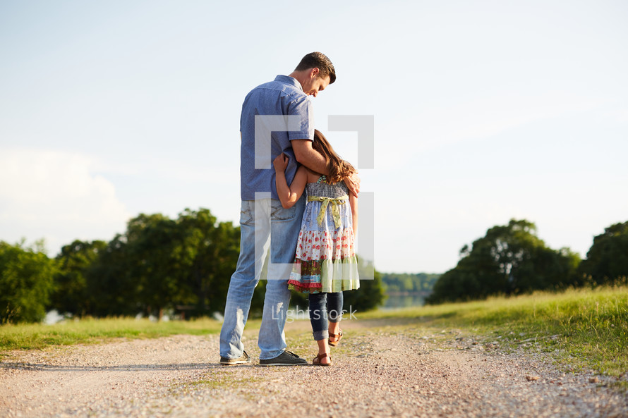 a father and his daughter walking down a dirt road together