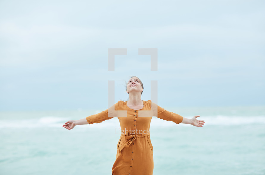 a woman standing on a beach with outstretched arms