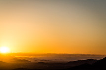 orange sky at sunset over mountain peaks
