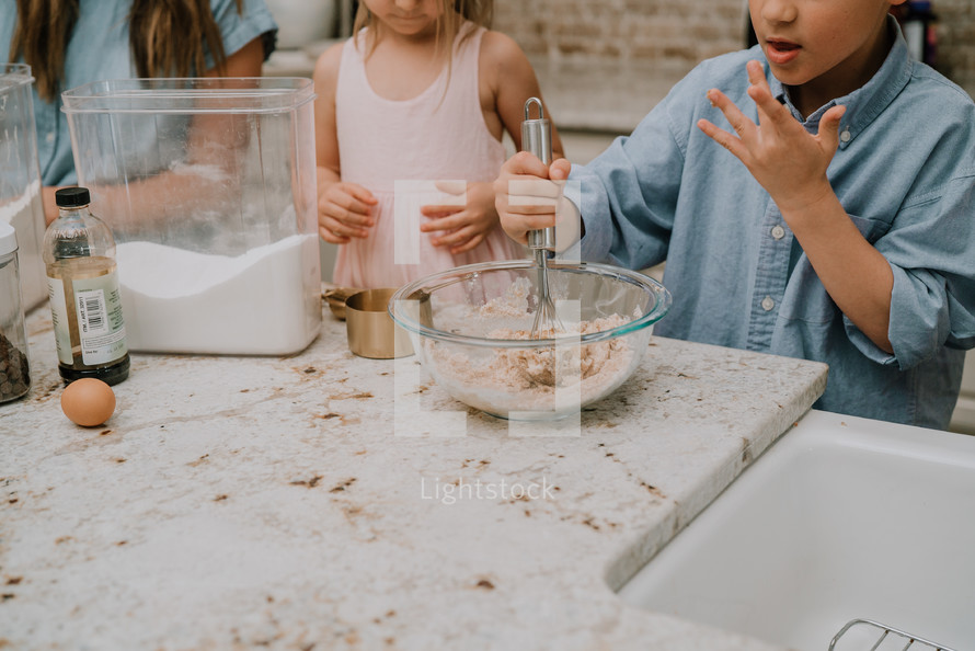 a mother baking cookies with her kids