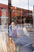 Young adults in a coffee shop window