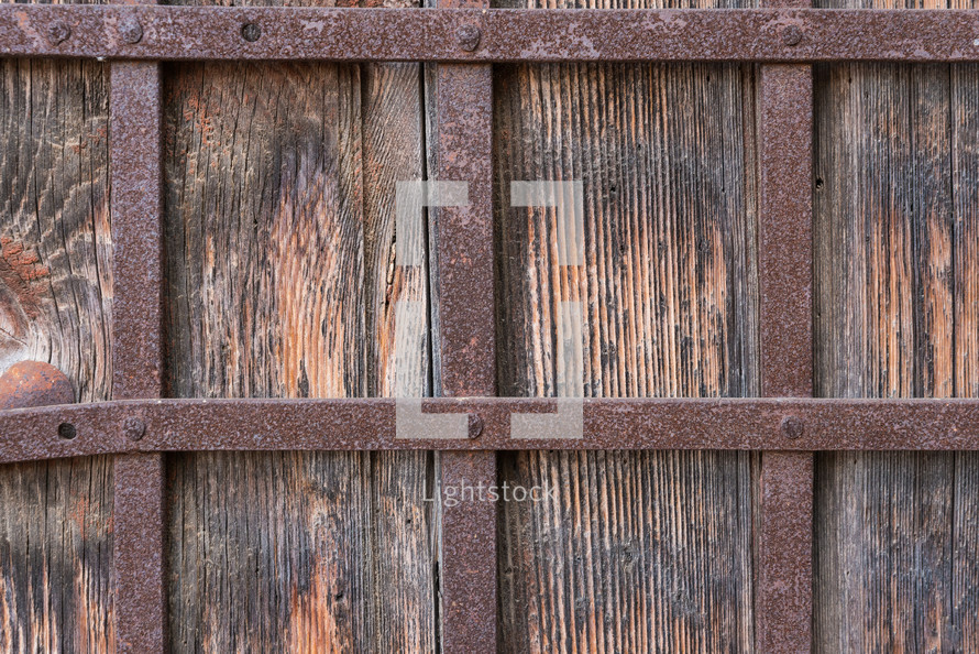 Close up of old wooden door with wrought iron bars