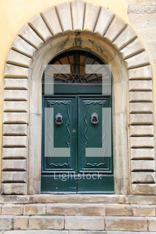 Wooden doors with door knocker in granite frame