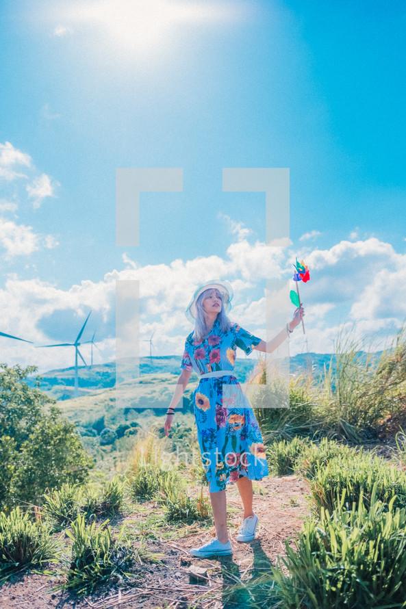 a woman holding pinwheels standing near wind turbines