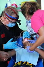 dentist and dental assistant working on a child