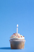 cupcake and candle against a blue background