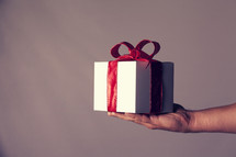 A hand holding out a gift box