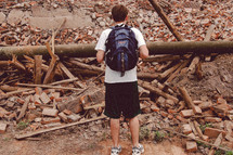 Teen with a backpack staring at debris.