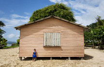 student in front of a small school house on a tropical island