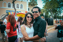 A couple with arms around each other at an outdoor festival.