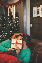 a couple snuggling under a blanket at Christmas and kissing behind a gift