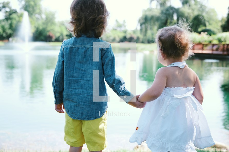 toddlers holding hands by a pond