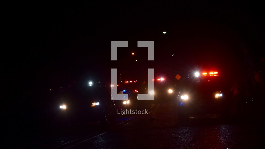 a line of police cars with flashing lights at night