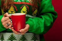 a woman in a Christmas sweater t-shirt holding a mug