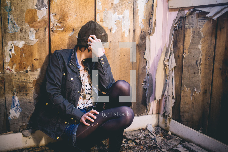 A woman sits on the floor of an abandoned house.