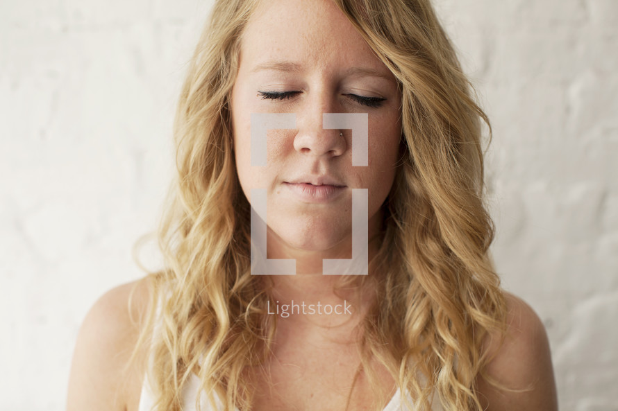 young blonde woman with closed eyes