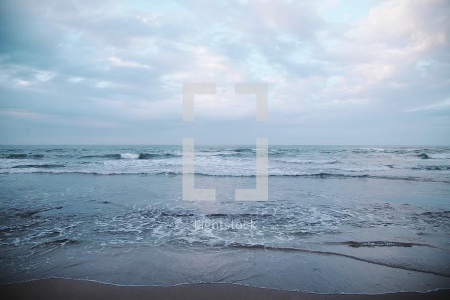 ocean water lapping onto a beach