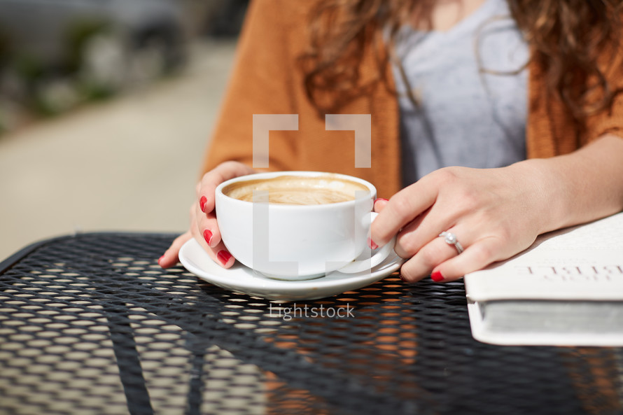 a woman sitting at an outdoor table with a Bible, drinking coffee