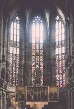 stained glass windows behind an altar in a cathedral