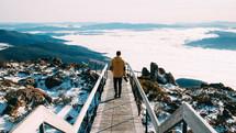 man walking on a boardwalk foot bridge towards the clouds