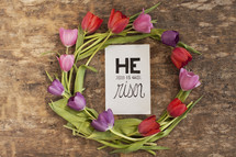 "Ring of tulips surrounding a ""He is risen"" card."