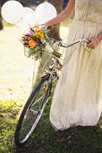a bride pushing a bicycle with a basket of flowers