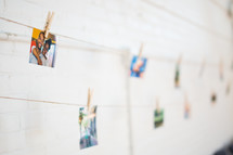 photos hanging in a display on a clothes line