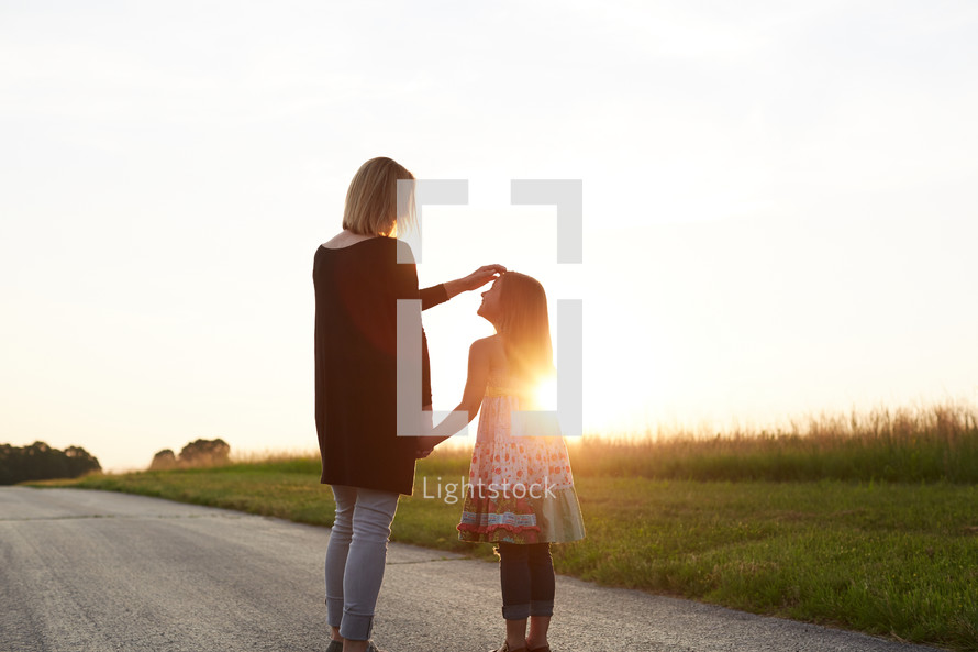 a mother and daughter standing together outdoors