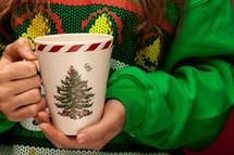 woman in a Christmas shirt holding a mug