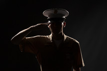 Soldier in uniform saluting.