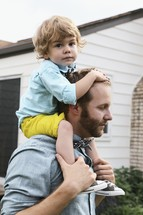 a father with his son on his shoulders