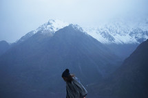 a woman walking in front of mountains
