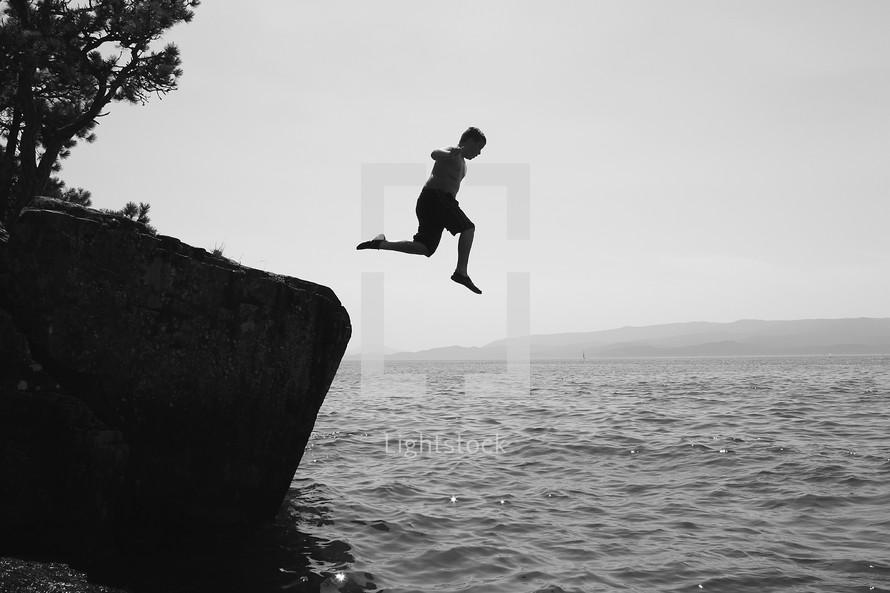man jumping into ocean water