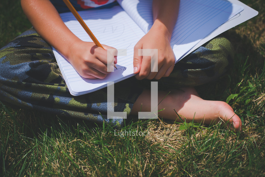 boy writing in a notebook sitting in the grass