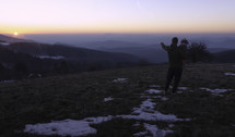 father holding his child and pointing to the sun rising behind mountains