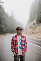 man in a ball cap and plaid shirt standing on the side of a road