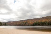 fall forest along a lake shore