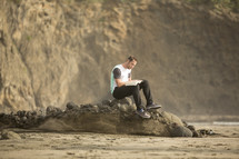 man sitting on rock reading a Bible on a beach
