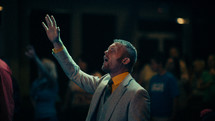 A man in suit and tie with hand raised in worship.