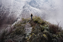a woman standing at the top of an icy mountain