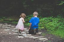 children looking under rocks outdoors