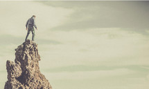 A man standing at the top of a rock formation.