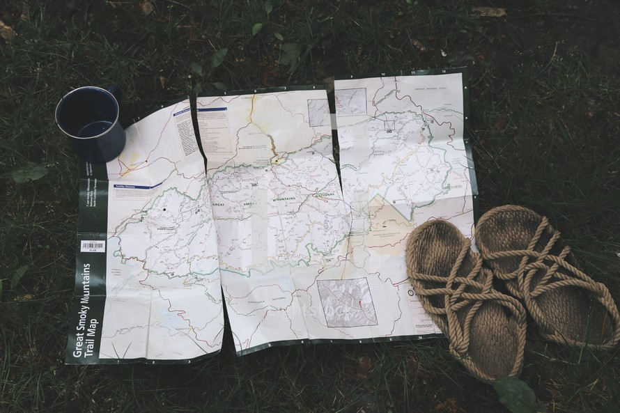 a trail map, sandals, and a coffee mug in grass