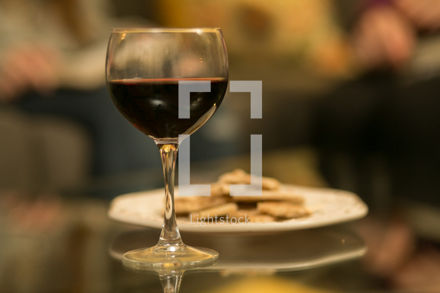 Glass of wine and a plate of crackers.