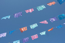 colorful banners hanging against a blue sky