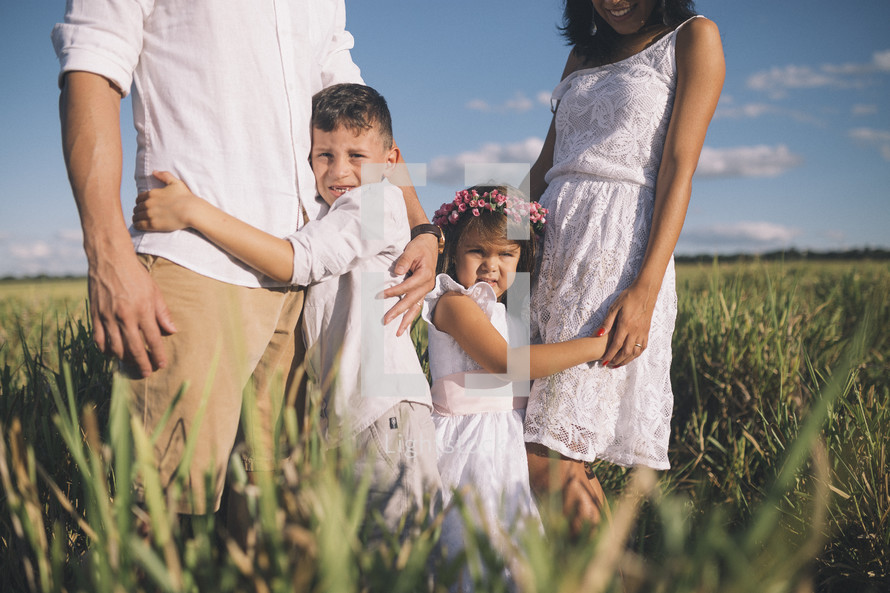 a family hugging in tall grass