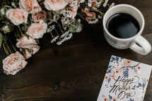 coffee cup, mother's day card, and flowers on wood