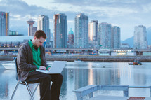 Man sitting on a chair with his laptop near an ocean bay by a city skyline.