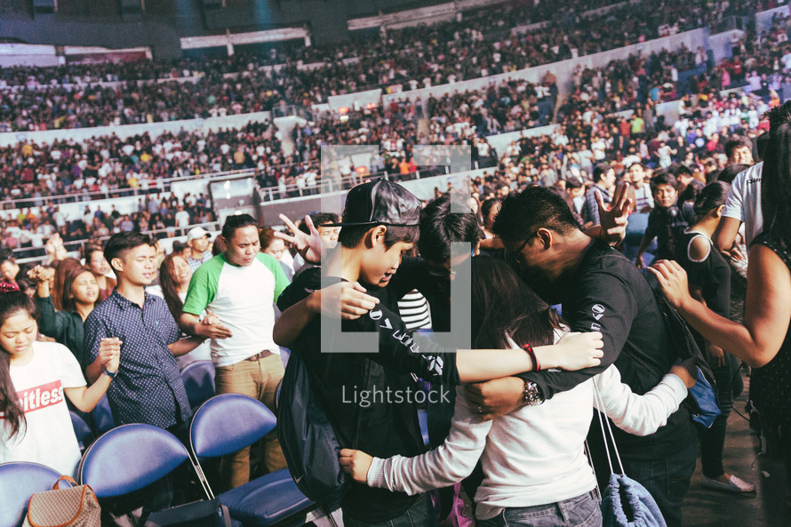people embracing at worship service in a stadium